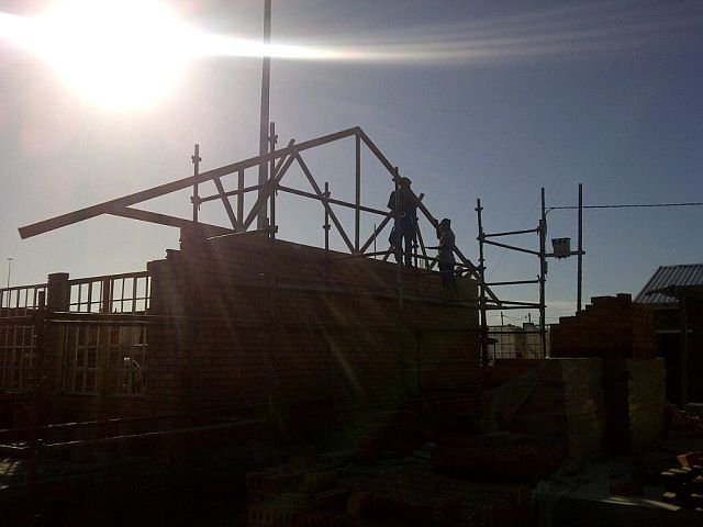 At daybreak, the 1st Truss is lifted into position on classroom block1